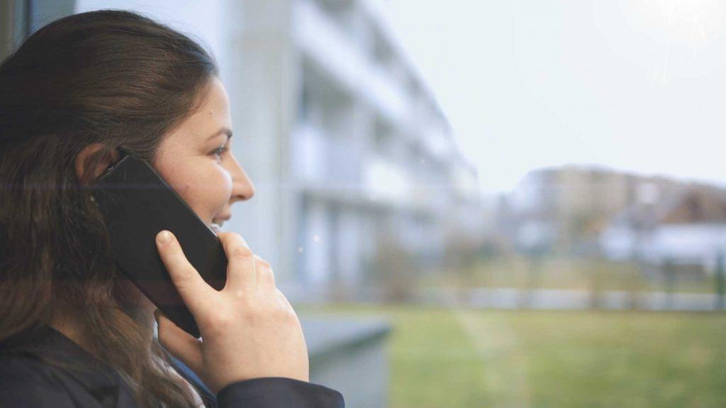 Coworkerin blickt beim Telefonieren aus dem Fenster des Coworking Space